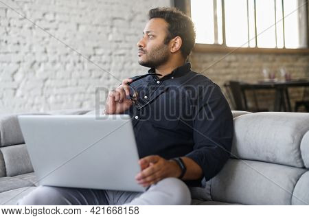 Contemplative Mixed-race Hindu Guy Sits On The Sofa With A Laptop And Waiting For Inspiration, Looks