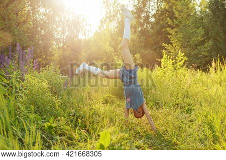 Teenage Girl Of 10-12 Years Old On The Grass In A Clearing Stands On Her Hands On A Summer Evening,