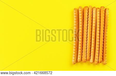 Grissini, Also Known As Breadsticks On Yellow Board, View From Above Space For Text Left Side