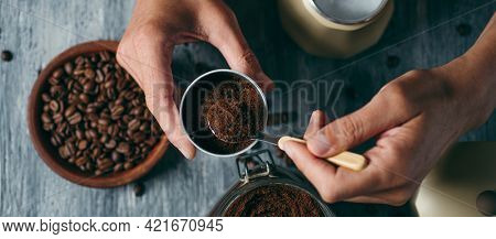 high angle view of a young caucasian man filling the funnel of a moka pot with ground coffee, at a gray rustic wooden table, in a panoramic format to use as web banner or header
