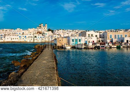 Picturesque view of Naousa town in famous tourist attraction Paros island, Greece with traditional whitewashed houses, Greek Orthodox church and moored fishing boats on sunset