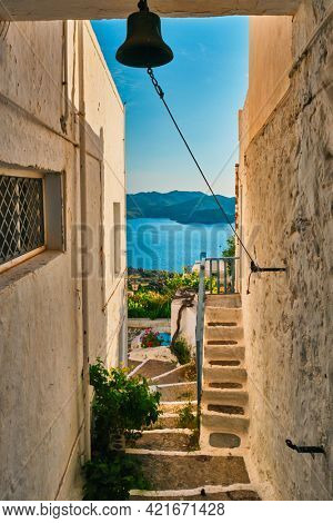 Greek village typical view with whitewashed houses and Aegean sea visible through arch and bell. Plaka town, Milos island, Greece