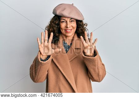 Middle age hispanic woman wearing french look with beret showing and pointing up with fingers number nine while smiling confident and happy.