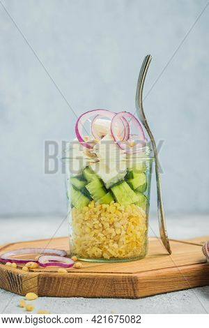 Healthy Salad With Bulgur, Feta And Fresh Vegetables In A Jar On A Wooden Board On A Light Concrete