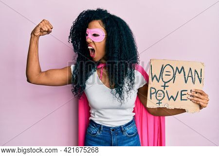 Middle age african american woman wearing super hero costume holding woman power banner angry and mad screaming frustrated and furious, shouting with anger. rage and aggressive concept.