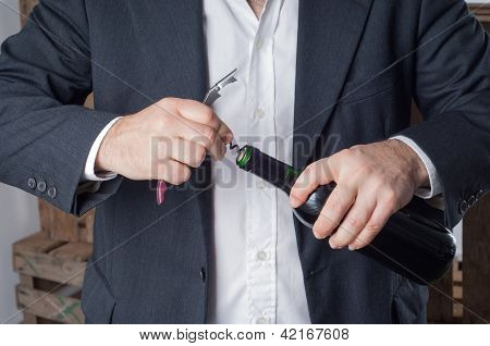 Man Opening A Red Wine Bottle