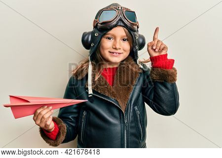 Little beautiful girl wearing pilot uniform holding paper plane smiling with an idea or question pointing finger with happy face, number one