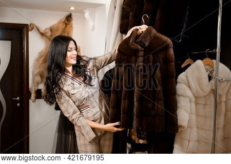 Attractive Woman In Fur Coat Shop With A Fur Coats On The Hanger