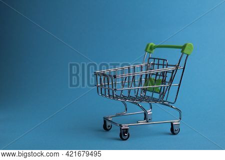 Shopping Cart On A Blue Background With A Copyspace. Purchases. Business. Buyer Demand. Shop. Buyers