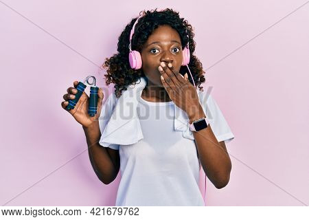 Young african american woman wearing workout clothes and holding hand grip covering mouth with hand, shocked and afraid for mistake. surprised expression