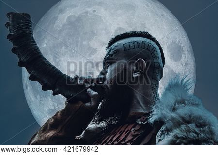 Brutal Viking Warrior Blowing Horn Outdoors Over Full Moon.
