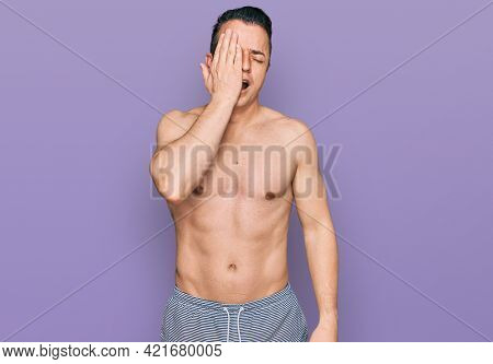 Handsome young man wearing swimwear shirtless yawning tired covering half face, eye and mouth with hand. face hurts in pain.