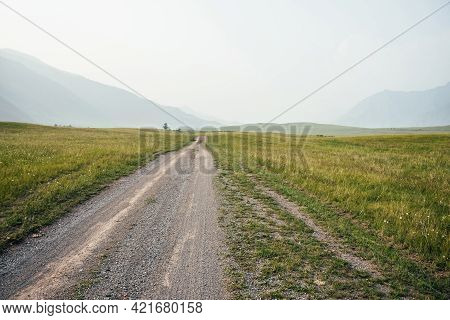 Beautiful Green Mountain Landscape With Long Dirt Road And Big Mountains In Fog. Atmospheric Foggy M