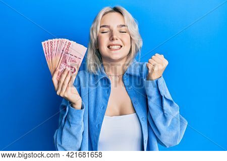 Young blonde girl holding thai baht banknotes screaming proud, celebrating victory and success very excited with raised arm