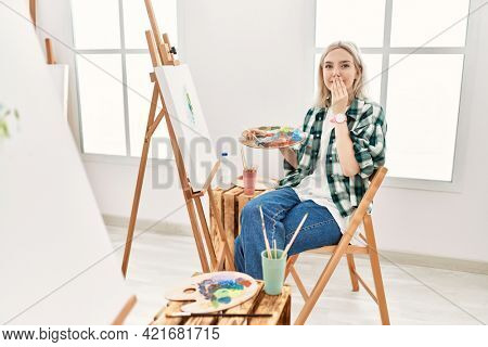 Young artist woman painting on canvas at art studio laughing and embarrassed giggle covering mouth with hands, gossip and scandal concept