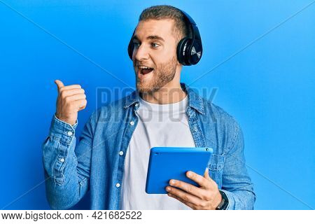 Young caucasian man using touchpad wearing headphones pointing thumb up to the side smiling happy with open mouth