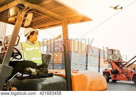 African-american Engineering Woman Supervises Field Work On Forklifts By Directing Shipping Work, Co