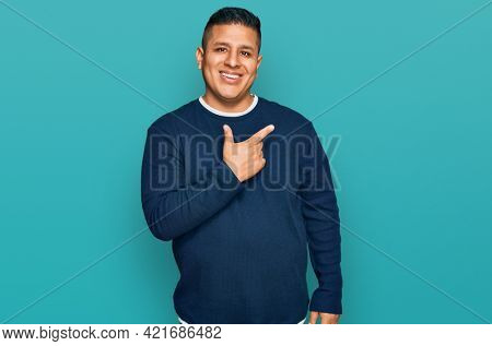 Young latin man wearing casual clothes cheerful with a smile of face pointing with hand and finger up to the side with happy and natural expression on face