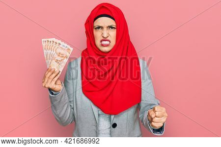Beautiful hispanic woman wearing islamic hijab holding turkish lira banknotes annoyed and frustrated shouting with anger, yelling crazy with anger and hand raised