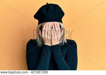 Young blonde girl wearing french look with beret with sad expression covering face with hands while crying. depression concept.