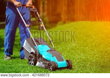 Close-up Of A Man In Overalls With A Lawn Mower Cutting Green Grass In A Modern Garden. Lawn Mowing