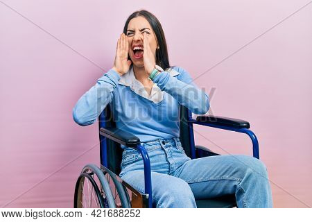 Beautiful woman with blue eyes sitting on wheelchair shouting angry out loud with hands over mouth