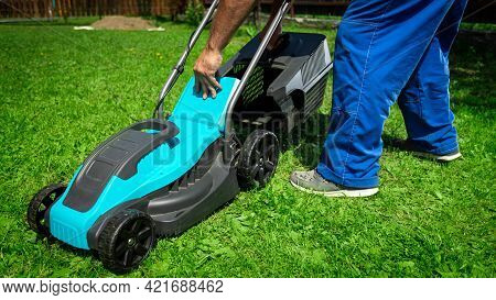 Lawn Grass Mowing. Worker Cutting Grass In A Green Yard. A Man With An Electric Lawn Mower Mowing A