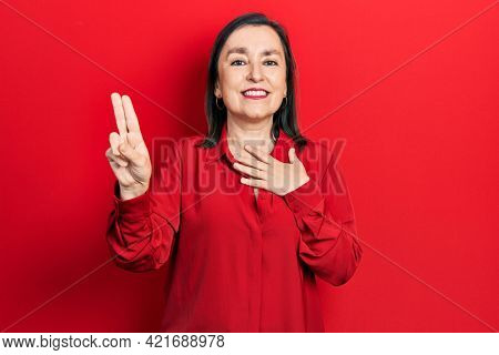 Middle age hispanic woman wearing casual clothes smiling swearing with hand on chest and fingers up, making a loyalty promise oath