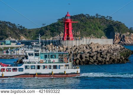 Sinjindo, South Korea; May 5, 2021: Fishing Charter Passing In Front Of Red Lighthouse Coming Into P