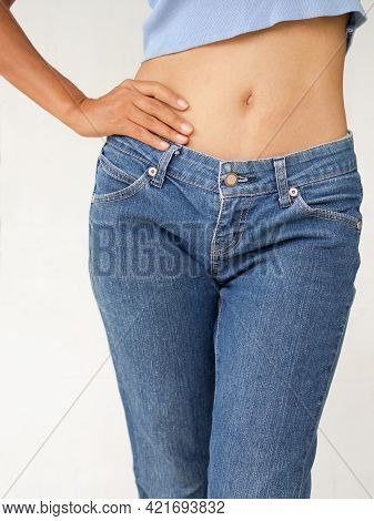Slim Woman With Jeans On White Background. Shapely Girl Young Waist Standing Close Up. Authentic Ski