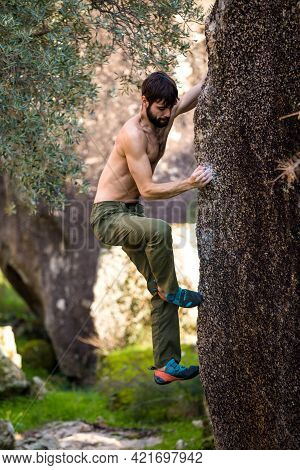 The Climber Climbs The Stone. The Athlete Is Engaged In Bouldering. Rock Climbing In Nature. The Con