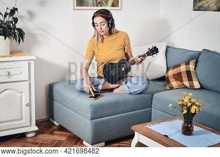 Woman playing ukulele at home. Domestic lifestyle. Woman relaxing at home. Hipster lifestyle. Beautiful woman at home. Lifestyle. Concept of easy living lifestyle. Happy people in at home. Relaxed people. Young people. Home decor. Playing music lifestyle.