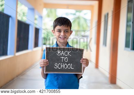 Smiling Young Kid Looking Camera And Showing By Back To School Sign Board School At Corridor - Conce