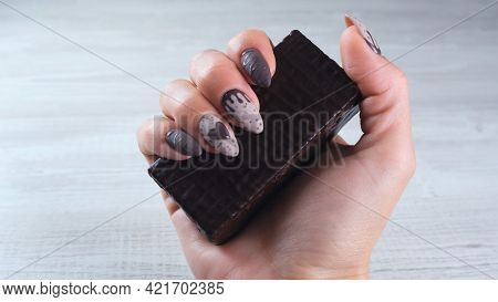 Female Hand With Beautiful Manicure Nails In The Form Of Chocolate Candies, Holding An Unrolled Bar
