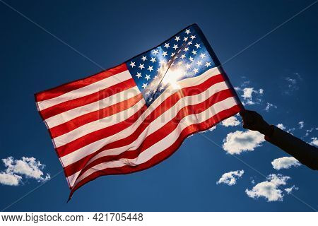 Waving America Flag Outdoors. Hand Holds Usa National Flag Against Blue Cloudy Sky. 4th July Indepen