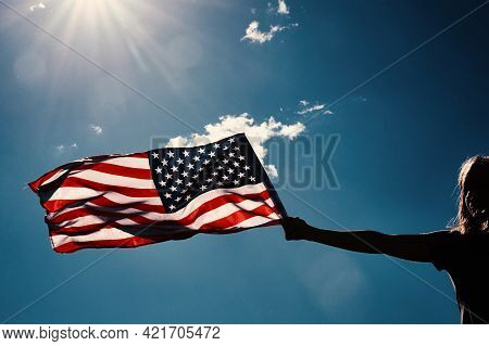 American Flag Outdoors. Woman Silhouette Holds Usa National Flag Against Blue Cloudy Sky. 4th July I