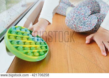 child playing with the Pop It fidget. Rainbow Pop it fidget toy