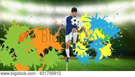 Composition of football player kicking ball over splodges and sports stadium background. sports event and competition concept digitally generated image.