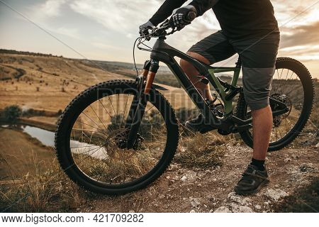 Side View Of Crop Anonymous Male Bicyclist Riding Modern Electric Mountain Bike Through Hilly Terrai
