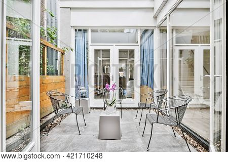 Opened Glass Doorway To Small Paved Yard With Garden Chairs And Wooden Fence In Daylight