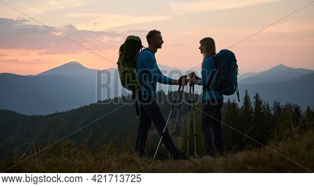Full Length Of Smiling Man And Woman Travelers Hiking Together In Mountains. Silhouette Of Happy You