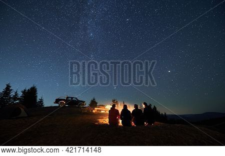 Evening Starry Sky Over Mountain Valley With Car And Hikers Near Campfire. Group Of Travelers Sittin