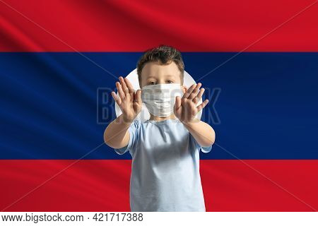 Little White Boy In A Protective Mask On The Background Of The Flag Of Laos Makes A Stop Sign With H
