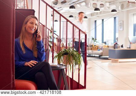 Businesswoman Sitting By Stairs In Modern Open Plan Office Talking On Mobile Phone