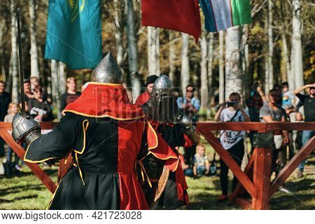 The Knight In Red Is Fighting With The Knight In Black. Sword Fighting. Reconstruction Of Medieval B