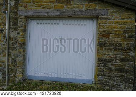 White Garage Door In A Brick Wall Close-up. Garage Building
