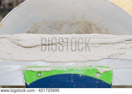 Gypsum Plaster On A Long Steel Spatula On A Bucket