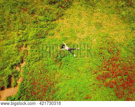 Aerial Top View Young Caucasian Woman Lay In Green Field Joyful Spreaded Hands. Well Being And Feeli