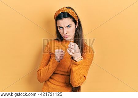 Young brunette teenager wearing casual yellow sweater ready to fight with fist defense gesture, angry and upset face, afraid of problem