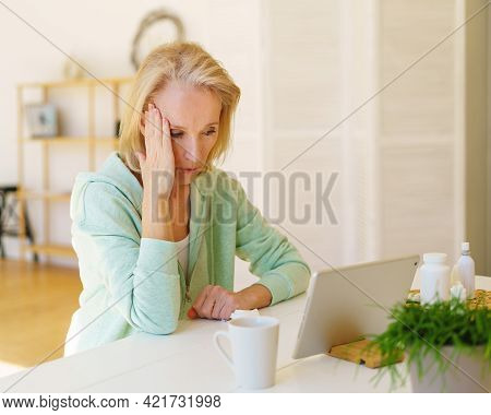 Modern Focused Middle Aged Woman Having Online Call With Doctor On Laptop Talking About Migraine, He